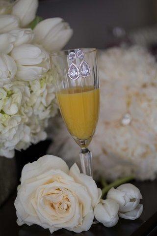 diamond-teardrop-earrings-on-crystal-champagne-flute-mimosa-orange-juice-glass