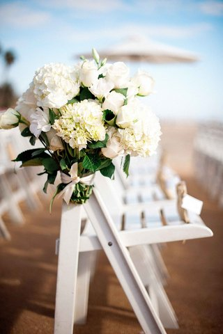 bouquet-of-white-hydrangeas-roses-on-folding-chair-at-beach-wedding-ceremony