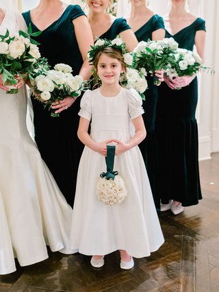 flower-girl-in-classic-white-dress-updo-flower-crown-holding-pomander-rose-bouquet-green-ribbon