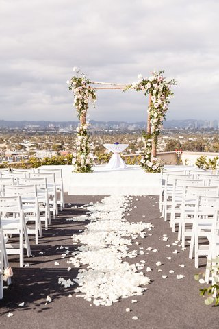 wedding-ceremony-on-rooftop-los-angeles-city-view-rustic-chuppah-arch-white-flower-petal-aisle-chair