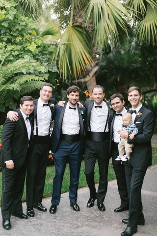 wedding-portrait-groomsmen-tuxedos-and-baby-in-plaid-shirt-bow-tie-groom-in-navy-tuxedo-black-lapel