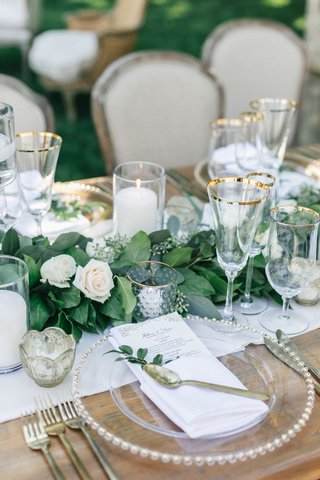 jillian-murray-and-dean-geyer-wedding-reception-wood-table-garland-candle-gold-rim-glassware