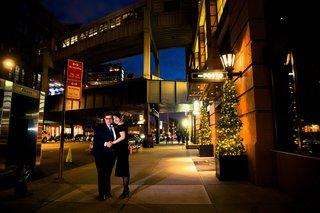 bride-in-a-black-oscar-de-la-renta-off-the-shoulder-dress-groom-in-navy-suit-at-del-posto-entrance