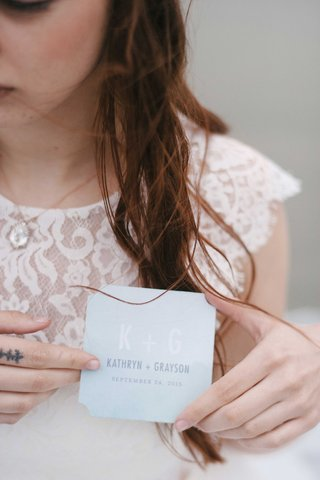 bride-held-a-blue-paper-product-with-the-bride-and-grooms-initials-names-and-the-wedding-date