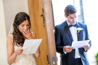 bride-puts-hand-up-to-mouth-and-groom-smiles-as-read-notes-on-opposite-sides-of-door