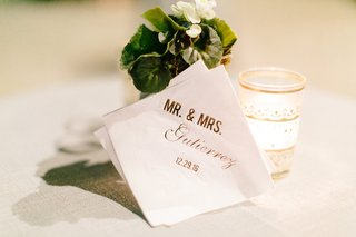 white-beverage-cocktail-napkin-with-gold-foil-writing-mr-and-mrs-gutierrez-wedding-date