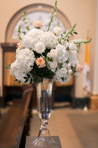 bouquet-of-white-hydrangeas-roses-snapdragons-and-light-orange-roses-in-a-tall-glass-vase