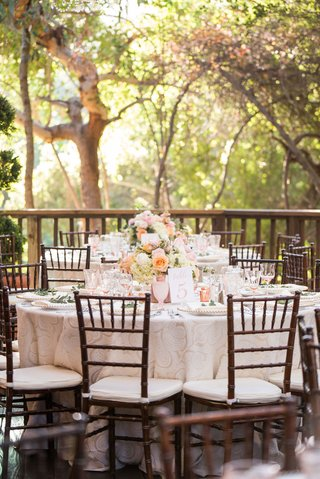 wedding-reception-wood-chair-white-cushion-low-centerpiece-pink-peach-flowers-goblets-glassware-tree