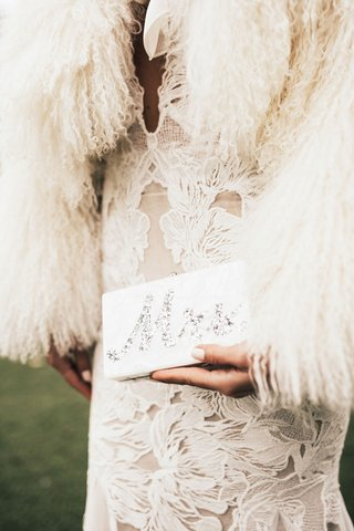 bride-in-wedding-dress-with-fur-wrap-holding-mother-of-pearl-silver-mrs-edie-parker-wedding-purse