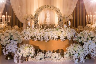 sweetheart-table-in-front-of-cake-table-with-hundreds-of-white-flowers-on-floor-and-table-as-decor