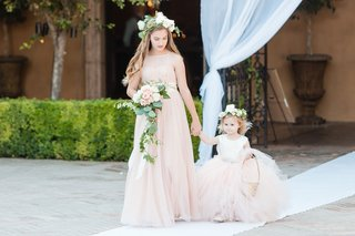 flower-girls-in-champagne-tulle-dresses-with-bouquet-and-flower-crowns-walking-down-white-aisle
