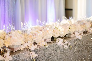 orchids-and-roses-line-head-table-with-silver-sequin-table-cloth-flower-garland-runner