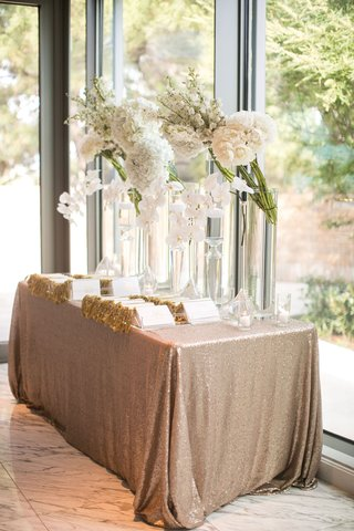 wedding-welcome-table-gold-sequin-linen-ceremony-programs-white-flowers-tall-glass-vases-rose-orchid