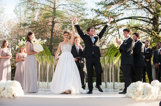 young-couple-raise-hands-in-celebration-after-ceremony