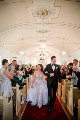 bride-in-kleinfeld-bridal-beaded-illusion-ball-gown-on-arm-of-husband-in-tuxedo-walking-up-aisle