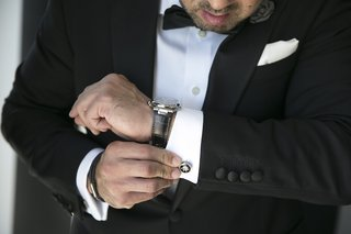 groom-in-black-tuxedo-wears-watch-with-black-band-puts-on-circurlar-cuff-links