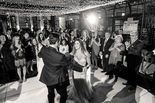 black-and-white-photo-of-bride-and-groom-dancing-guests-watching-first-dance-under-string-lights