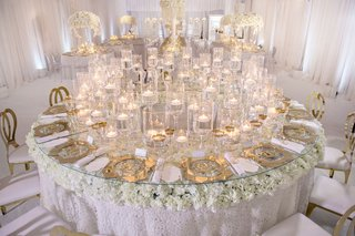 round-table-with-textured-linens-white-flowers-and-glass-tabletop-floating-candles-gold-chargers