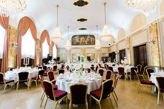 destination-second-wedding-in-germany-burgundy-gold-guest-chairs-white-centerpiece-gold-chandeliers