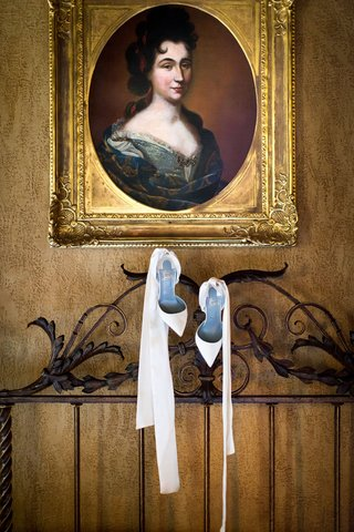 wedding-shoes-hanging-from-headboard-under-gold-portrait-frame-white-christian-louboutin-pumps