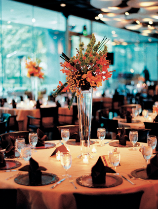 wedding-reception-centerpiece-of-orange-and-green-flowers-in-a-tall-vase
