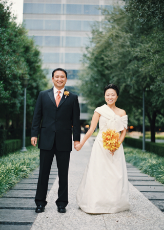 bride-in-a-strapless-dress-with-a-burberry-wrap-and-groom-in-a-black-tuxedo-and-orange-tie
