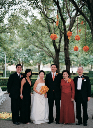 bride-in-strapless-dress-and-groom-in-black-tuxedo-and-orange-tie-with-family