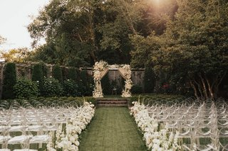 wedding-ceremony-on-grass-lawn-seattle-ghost-clear-chairs-white-flowers-chuppah-drapes-neutral-decor