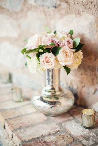 stone-wall-with-brick-mantle-silver-vase-metallic-candle-holder-pink-rose-white-hydrangea-flower