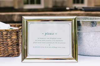 white-sign-with-green-type-in-silver-frame-instructing-guests-to-not-take-photos-during-the-ceremony