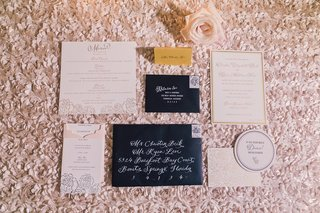gold-escort-card-black-envelope-with-white-calligraphy-pink-and-white-peony-wedding-design-invite