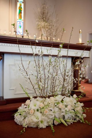 altar-decorated-with-light-colored-flowers-and-cherry-blossom-branches-for-a-wedding