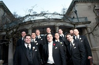 groom-in-black-tuxedo-white-vest-red-rose-boutonniere-with-groomsmen-in-black-tuxedos