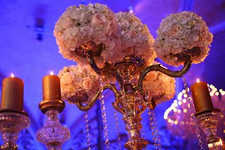 wedding-reception-centerpiece-of-golden-candelabra-with-light-flowers-surrounded-by-golden-candles