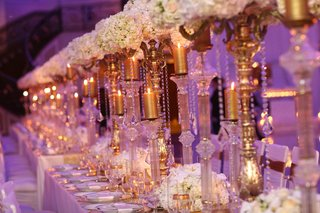 wedding-reception-table-with-golden-candelabra-candles-and-gold-rimmed-glassware-and-chargers