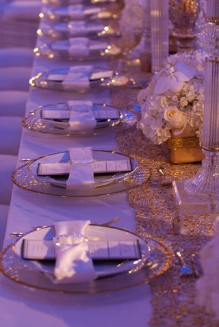 wedding-reception-place-setting-with-gold-rimmed-dinnerware-and-satin-white-napkin-with-crystal-ring
