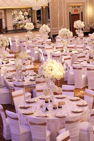 wedding-reception-with-white-floral-arrangements-and-chair-sleeves-with-gold-ribbons
