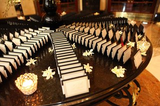 wedding-place-card-table-with-black-and-white-cards-white-flowers-and-candles