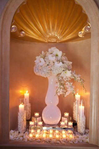 wedding-reception-wall-niche-with-vase-and-white-flowers-and-votive-candles