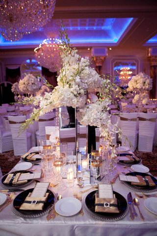 wedding-reception-table-with-tall-mirrored-vases-and-white-flowers-silver-beaded-rimmed-chargers