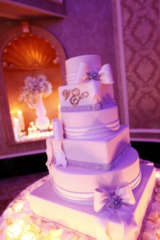 white-wedding-cake-with-crystals-and-fondant-ribbons-surrounded-by-candles