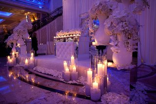 wedding-reception-with-fabric-draped-alcove-for-bride-and-groom-with-white-flowers-and-candles