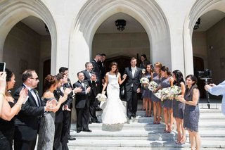 bridesmaids-and-groomsmen-create-pathway-on-stairs-for-newlyweds