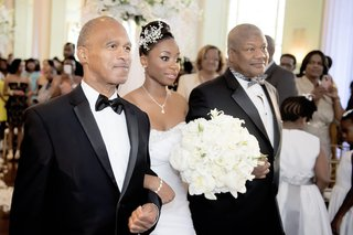 african-american-bride-with-headpiece-walks-down-aisle-with-two-dads