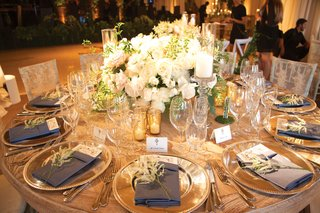 wooden-table-with-white-roses-in-centerpiece-gold-votives-navy-napkins-with-amaranthus