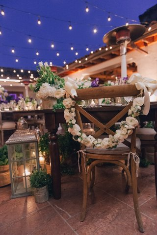 wooden-chair-with-white-flower-garland-and-ribbon