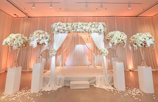 ivory-blush-peach-flower-arrangements-on-white-stands-and-ceremony-altar-peach-uplighting