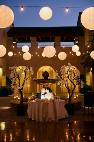 bride-and-groom-kiss-at-sweetheart-table-trees-frame-sweetheart-table-paper-lanterns