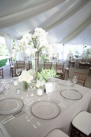 reception-table-with-white-flowers-green-leaves-glass-plates-glasses-white-candles