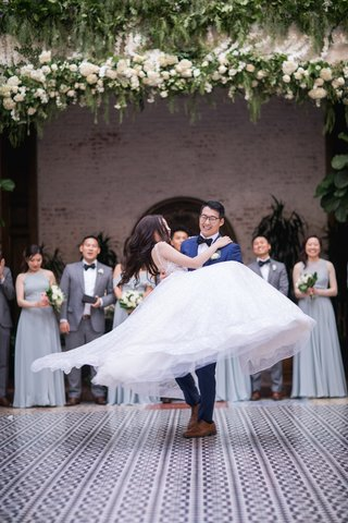 groom-lifting-bride-in-ball-gown-and-spinning-her-in-the-air-during-first-dance